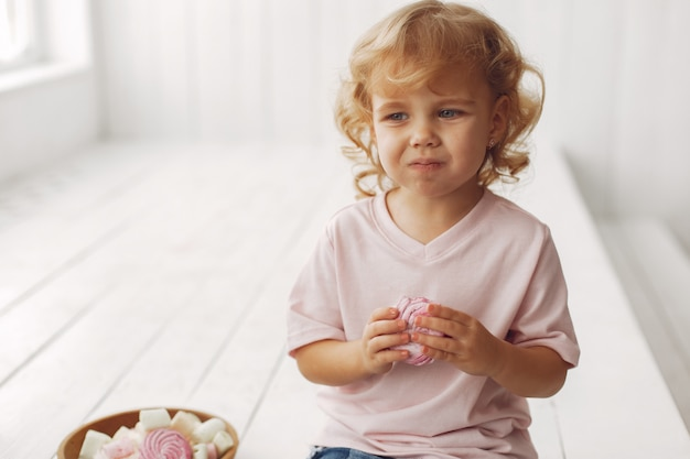 Cute little girl sitting and eating cookies