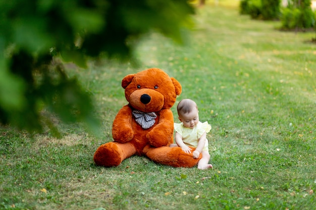 Cute little girl sitting on green grass with big teddy bear in yellow summer dress in summer