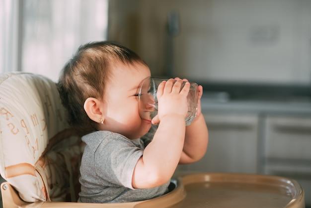 キッチンのベビーチェアに座って水を飲むかわいい女の子