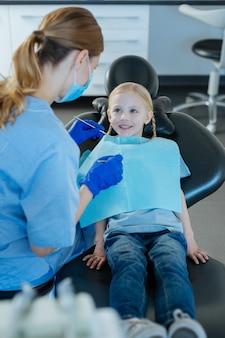 Милая маленькая девочка сидит в кресле стоматолога и проходит осмотр полости рта молодой женщиной-стоматологом с помощью ротового зеркала и стоматологического зонда