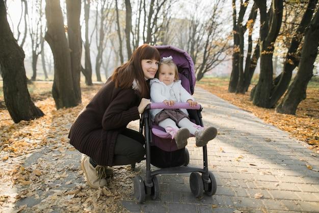 그녀의 어머니 옆에 보라색 유모차에 앉아 귀여운 소녀