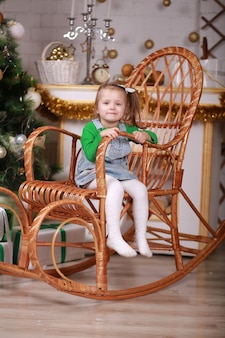 Милая маленькая девочка сидит в кресле-качалке возле елки.