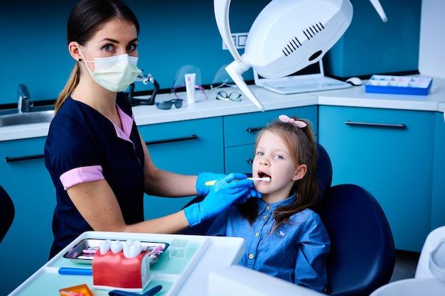 歯科医院に座っているかわいい女の子