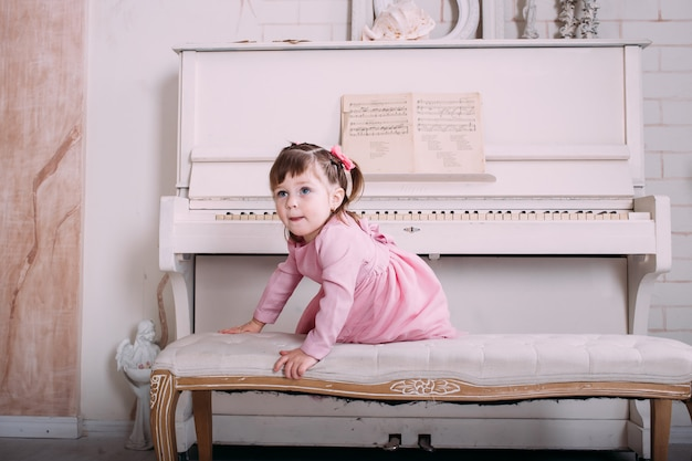 Cute little girl sitting near piano at home