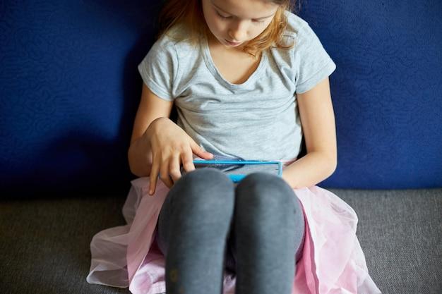 Милая маленькая девочка сидит на диване, малыш увлекается технологиями, любит играть в онлайн-игры на цифровом планшетном компьютере, использовать приложения, просматривать информацию в интернете дома,