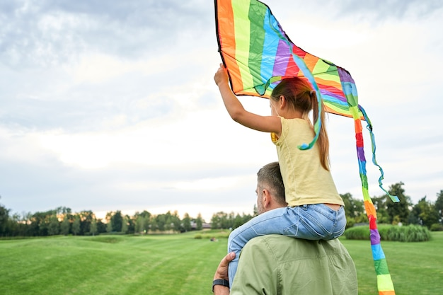 父親の肩に座って、美しい緑の公園でカラフルな凧を保持しているかわいい女の子