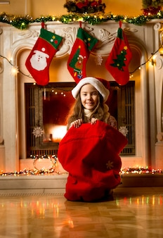 Cute little girl sitting in santa red bag at fireplace