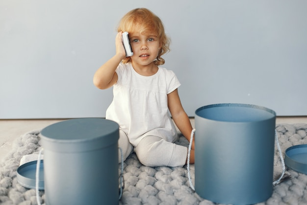 Cute little girl sitting in a studio with presents box