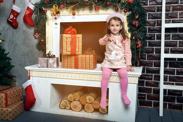 Cute little girl sitting on a white fireplace near the christmas tree with a lot of gifts.