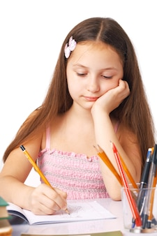 Cute little girl sketching something in the copybook