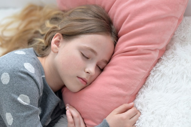 침대에서 자고 있는 귀여운 소녀