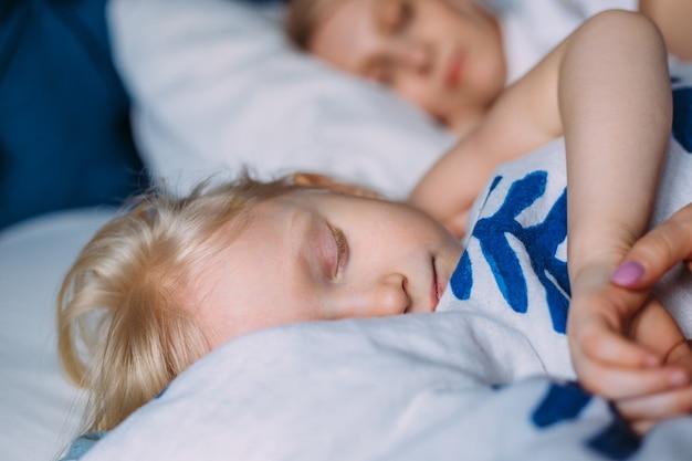ベッドで母親と一緒に寝ているかわいい女の子。インテリア。コンセプトケア