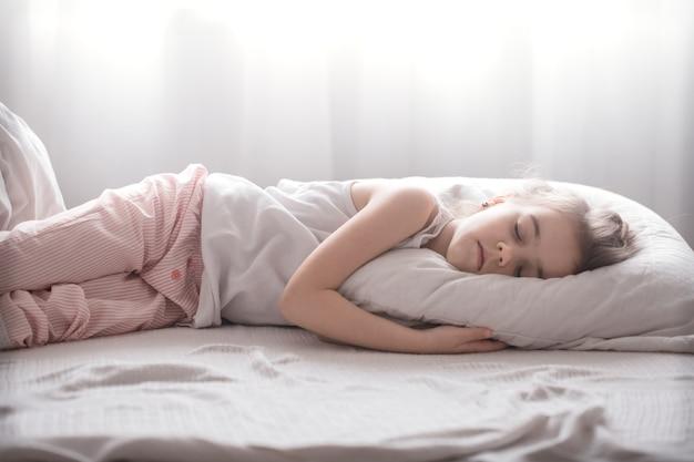 귀여운 소녀는 흰색 아늑한 침대, 어린이 휴식과 수면의 개념에서 달콤하게 잔다.
