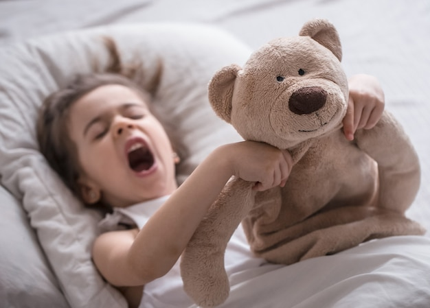 Cute little girl sleeps sweetly in a white cozy bed with a soft bear toy, the concept of children's rest and sleep