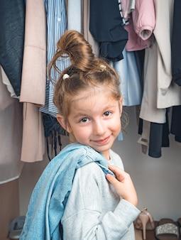 옷장에 옷걸이에 옷의 배경에 귀여운 소녀 미소.