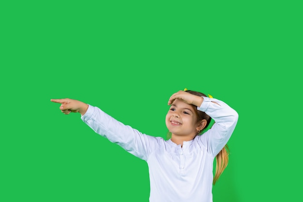 A cute little girl smiles looks into the distance and shows her index finger green isolated background