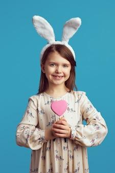 Милая маленькая девочка улыбается и держит печенье в форме сердца
