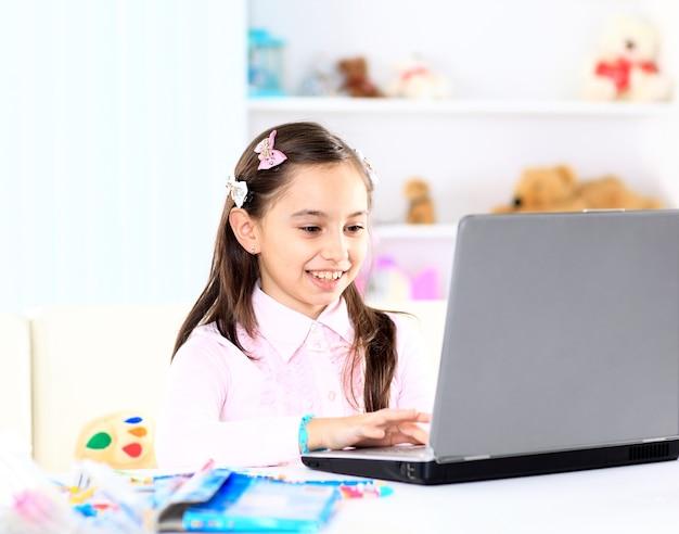 Милая маленькая девочка улыбается и смотрит на ноутбук