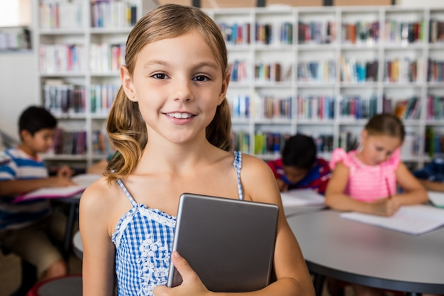 A cute little girl smiling at the camera with tablet pc