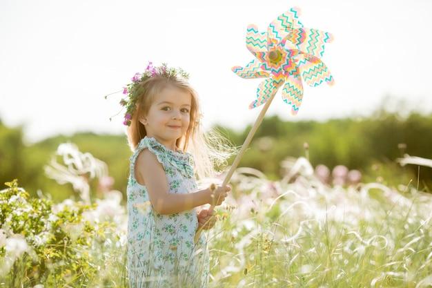 風車を保持しているフィールドで夏の笑顔かわいい女の子