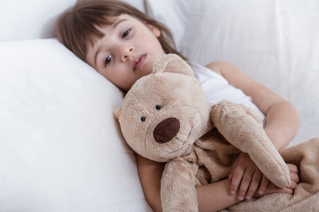 Cute little girl smiling while lying in a cozy white bed