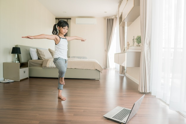 Cute little girl in sportswear watching online video on laptop and doing fitness exercises at home.