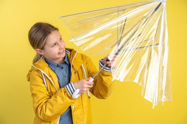 かわいい女の子が黄色い壁に傘を広げます
