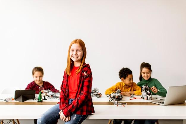 ロボット工学の教室で電気おもちゃやロボットをプログラミングする子供たちのグループの前に立っているかわいい女の子