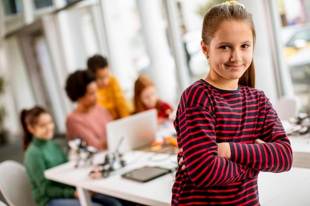 로봇 교실에서 전기 장난감과 로봇을 프로그래밍하는 아이들의 그룹 앞에 서있는 귀여운 소녀