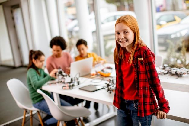 Милая маленькая девочка стоит перед группой детей, программирующих электрические игрушки и роботов в классе робототехники