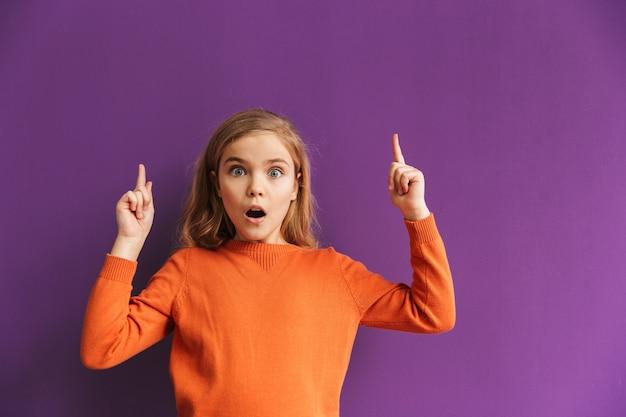 Милая маленькая девочка, стоящая изолированно над фиолетовой стеной, указывая вверх