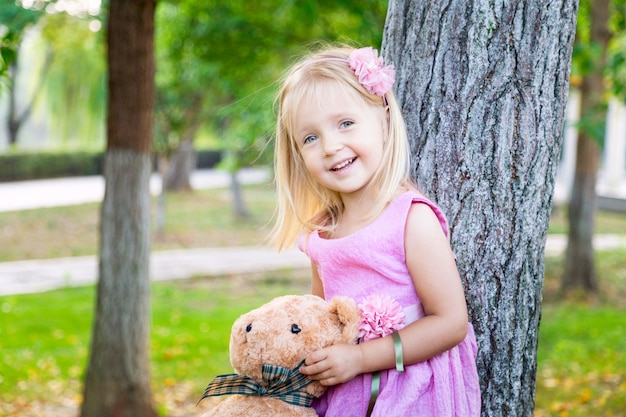 Cute little girl standing near tree with her teddy bear