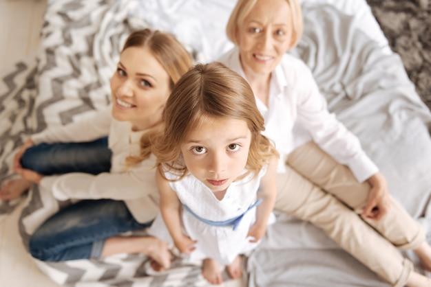 귀여운 소녀가 침대에 서서 그녀의 어머니와 할머니가 그녀의 뒤에 앉아 웃고있는 동안 조금 무서워하는 것처럼 호기심 많은 표정으로 앞을보고 있습니다.