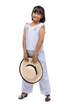Cute little girl standing in swimming wear and hat on white