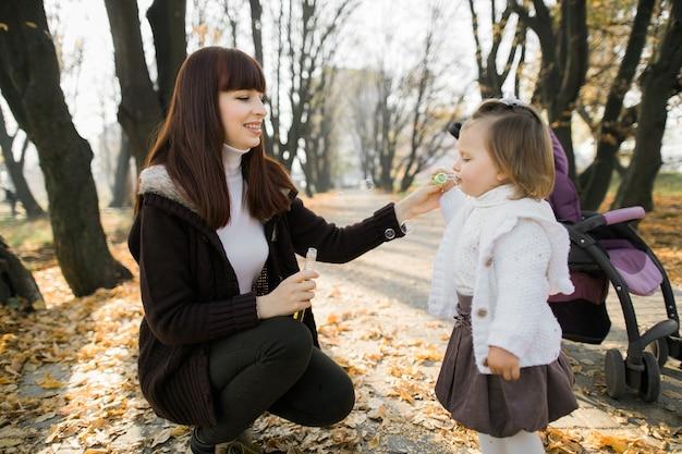 그녀의 어머니의 손을 잡고 서있는 귀여운 어린 소녀