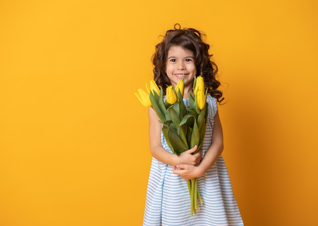Cute little girl in striped dress holds bouquet of tulips on yellow studio background. spring woman day.