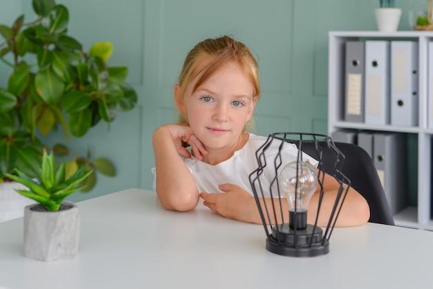 Милая маленькая девочка-студентка делает домашнее задание дома онлайн