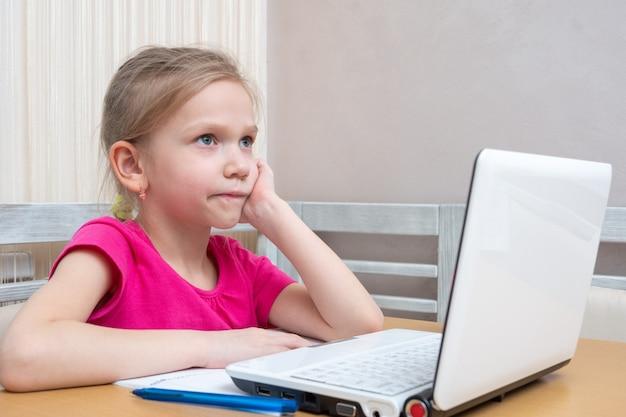 Милая маленькая девочка-студентка сидит за столом и думает, как делать домашнее задание