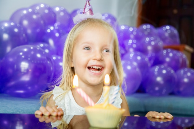 Cute little girl in stylish dress celebrating birthday day with purple balloons
