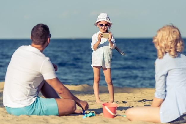 Cute little girl in sun glasses is taking photo.