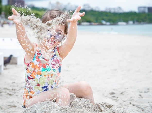 La bambina sveglia in occhiali da sole gioca con la sabbia di mare sulla spiaggia.