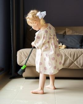 Милая маленькая девочка подметает пол метлой дома