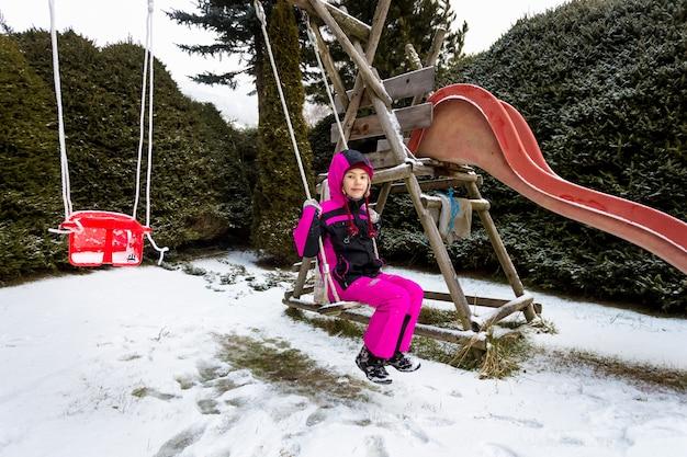 Милая маленькая девочка качается на детской площадке в холодный снежный день