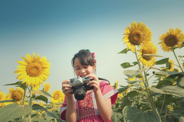 Cute little girl takes picture with vintage camera in sunflower field.