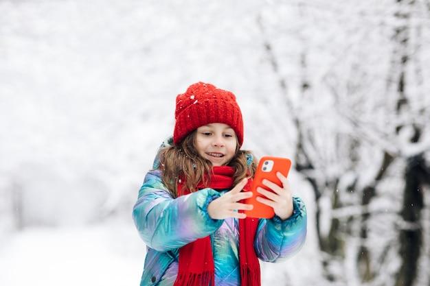 Cute little girl taking a selfie in the winter forest.
