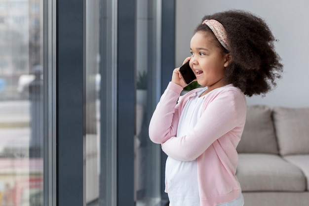 Cute little girl talking on the phone at home