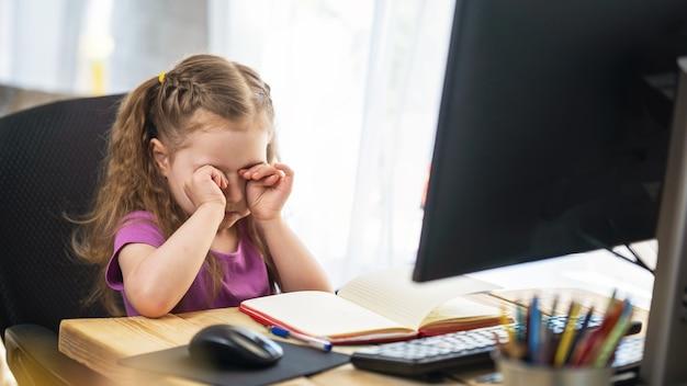 コンピューターをリモートeラーニングに使用しているかわいい女の子が目をこする