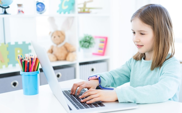 Cute little girl using computer in light room
