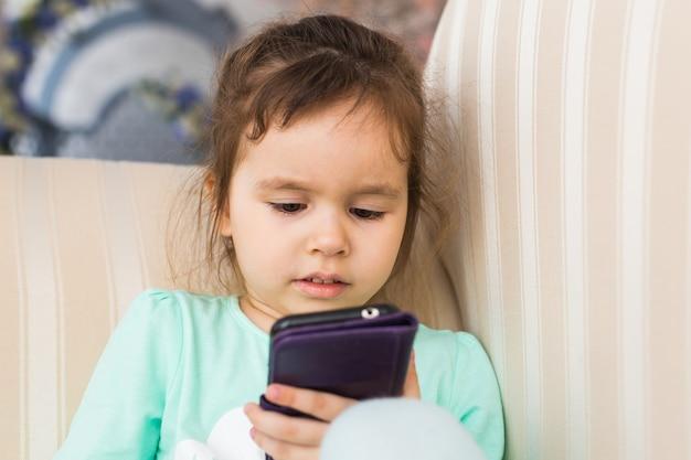 방에 현대적인 스마트 폰을 사용 하여 귀여운 소녀