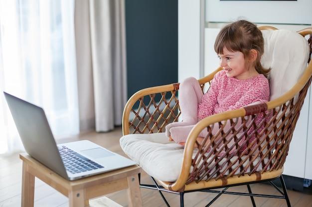 Милая маленькая девочка разговаривает по видео с бабушкой и дедушкой, используя ноутбук
